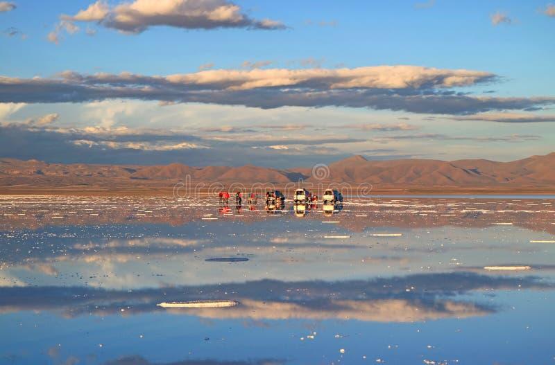 人们享受在乌尤尼盐沼盐舱内甲板的镜子作用的活动在雨季,玻利维亚结束时 库存照片