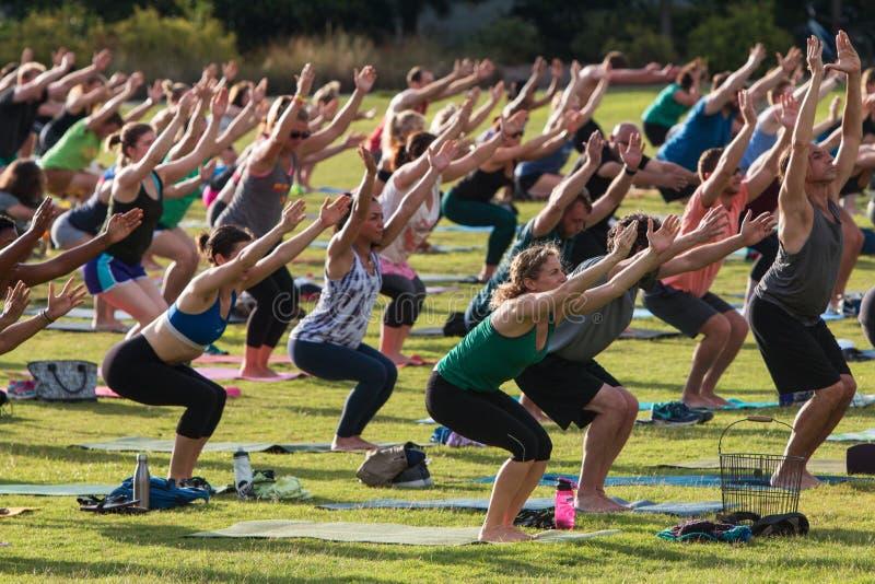 人们做在室外小组瑜伽类的Utkatasana姿势 库存图片