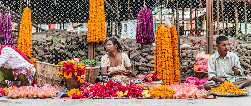 人们卖花项链近到加德满都Durbar广场 库存图片