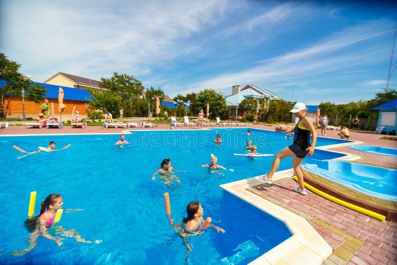 人们参与在水池的水上体操 免版税图库摄影