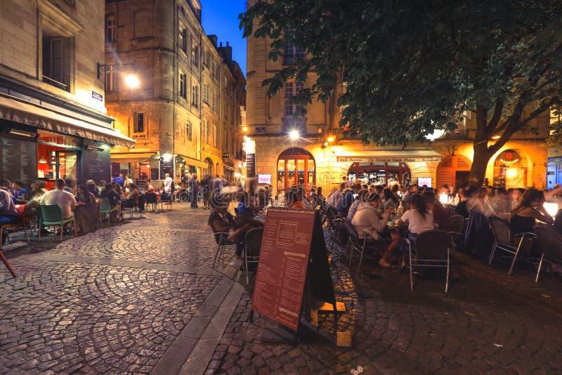 人们吃饮料和晚餐在餐馆大阳台在红葡萄酒街市 库存照片