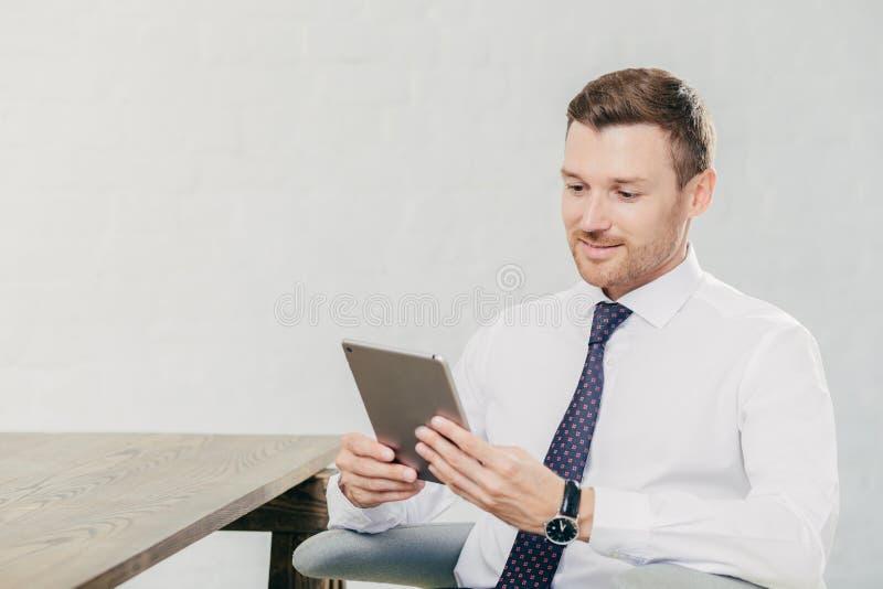 人们和企业概念 在正式成套装备的年轻商人为读的财务新闻在互联网,被连接的t使用触摸板 免版税库存图片