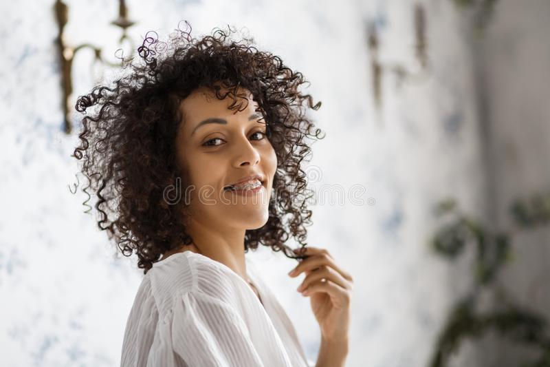 人们和幸福概念 微笑对照相机的快乐的非裔美国人的少妇显示她有括号的ultrawhite牙 免版税库存照片