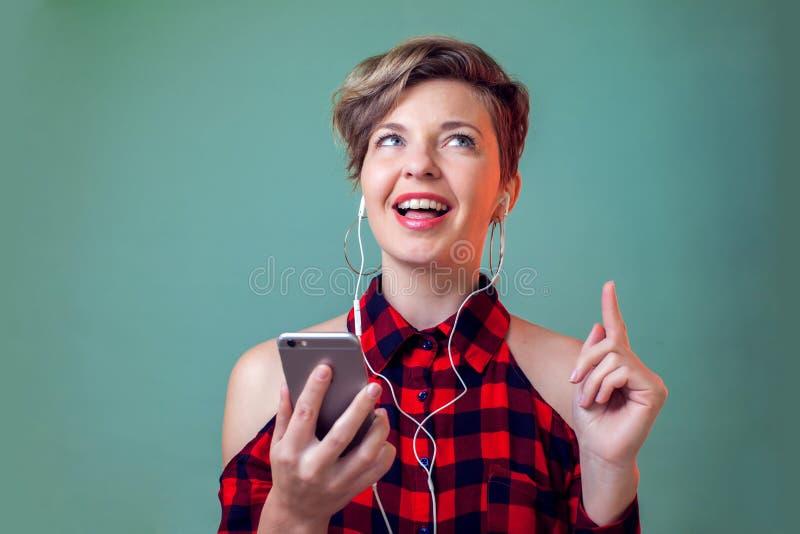 人们和情感-有短发的在耳机听到音乐的微笑的妇女画象  免版税库存图片