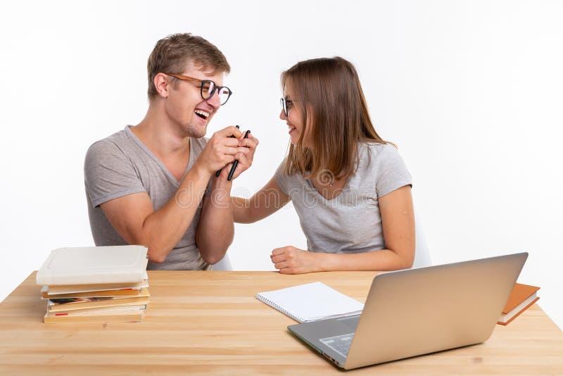 人们和教育概念-两名学生获得乐趣,当工作时 免版税图库摄影
