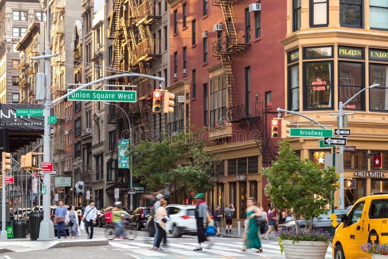人们和汽车在曼哈顿纽约横渡百老汇的一个繁忙的交叉点沿联合广场公园 库存图片