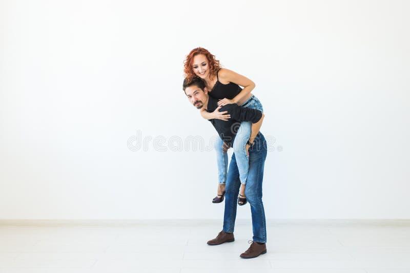 人们和爱概念-坐在人的后面和拥抱他的美丽的俏丽的妇女在与拷贝的白色背景 免版税图库摄影