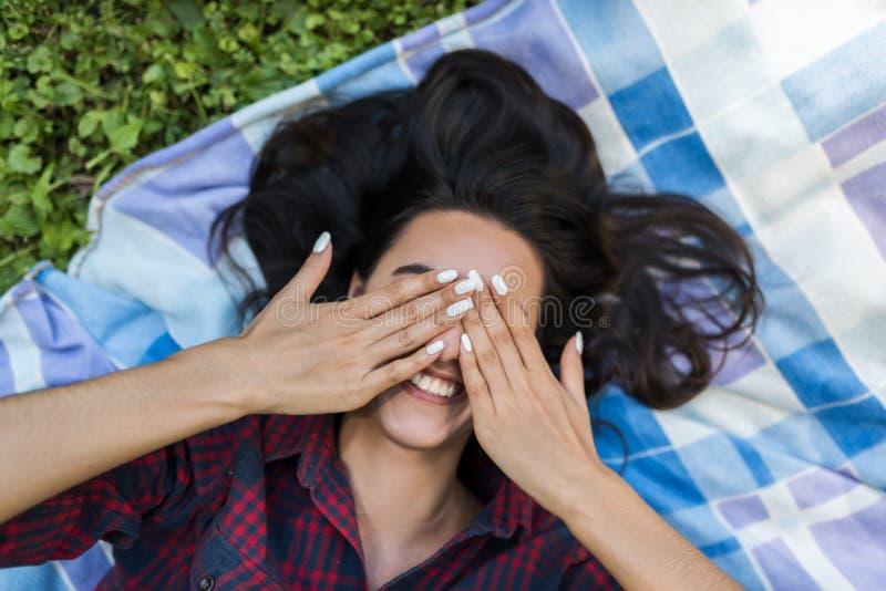 人们和生活方式概念 年轻可爱的深色的女性佩带的格子衬衫皮眼睛顶视图用手和微笑 库存图片