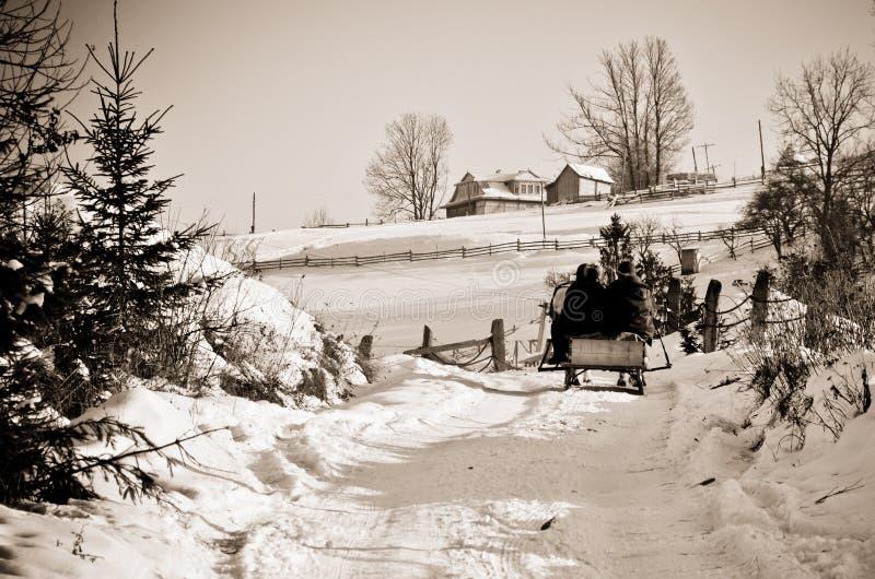 人们在冬天去sledding回家在雪路在山 免版税库存照片