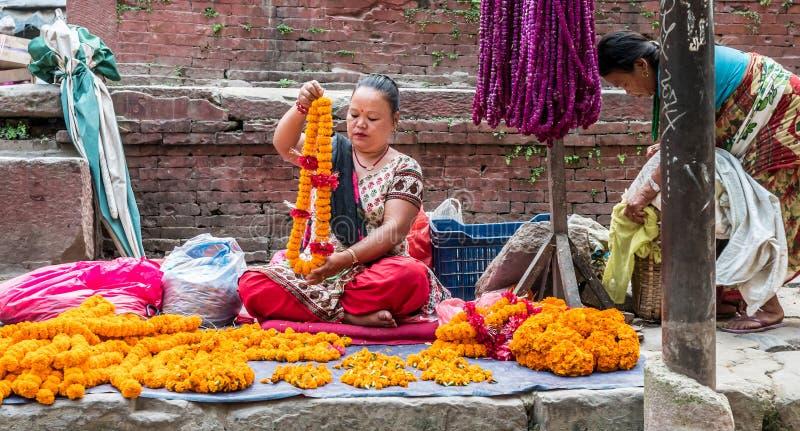 人们在加德满都Durbar广场旁边卖花项链 图库摄影
