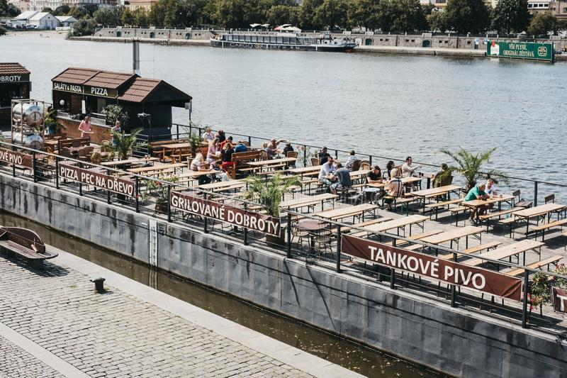 人们在咖啡馆的桌上坐伏尔塔瓦河河在布拉格,捷克 库存图片