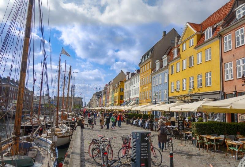 人们在哥本哈根丹麦漫步Nyhavn地区鹅卵石街道  免版税图库摄影