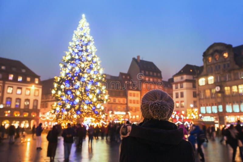 人们在圣诞节市场上,看xmas树的妇女在夜之前 库存图片