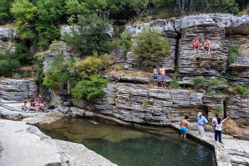 人们在岩石的自然小湖游泳 免版税库存图片