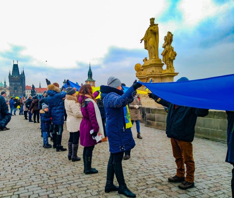 人们在布拉格组织了在查理大桥的一个生存链子 免版税库存照片