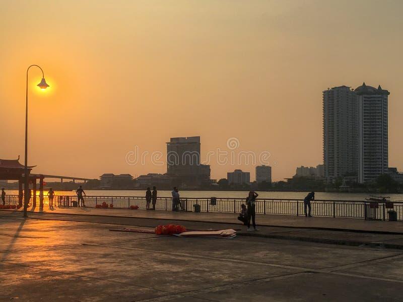 人们在有照亮灯笼的金黄日落美丽的树荫的广场 免版税库存图片