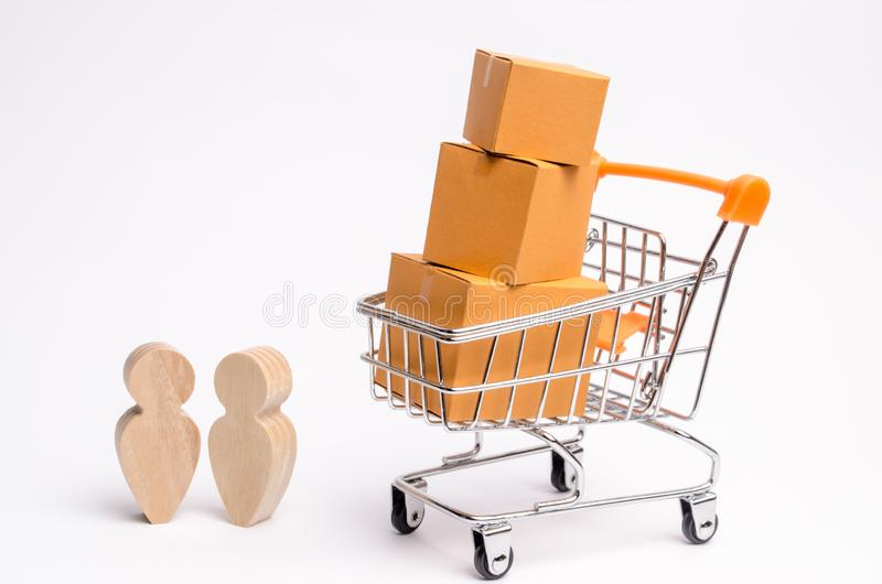 人们在有纸板箱的商业独轮车附近站立和谈话 物品运输和交付的服务  库存照片