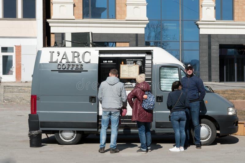 人们在轮子的一流动咖啡馆,汽车买咖啡装备做的咖啡特别设备在城市街道 免版税库存照片