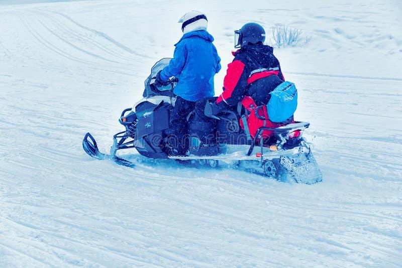 人们在雪上电车和冬天圣诞节的芬兰拉普兰 图库摄影