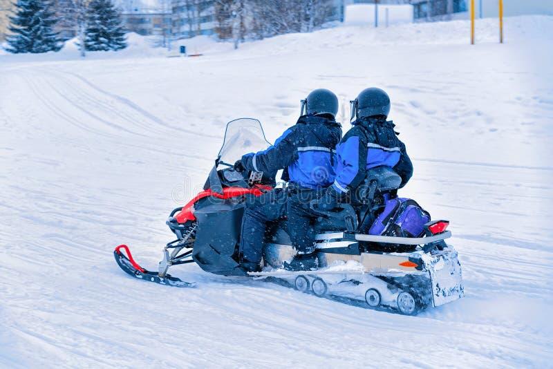 人们在雪上电车和冬天圣诞节的芬兰拉普兰 库存图片