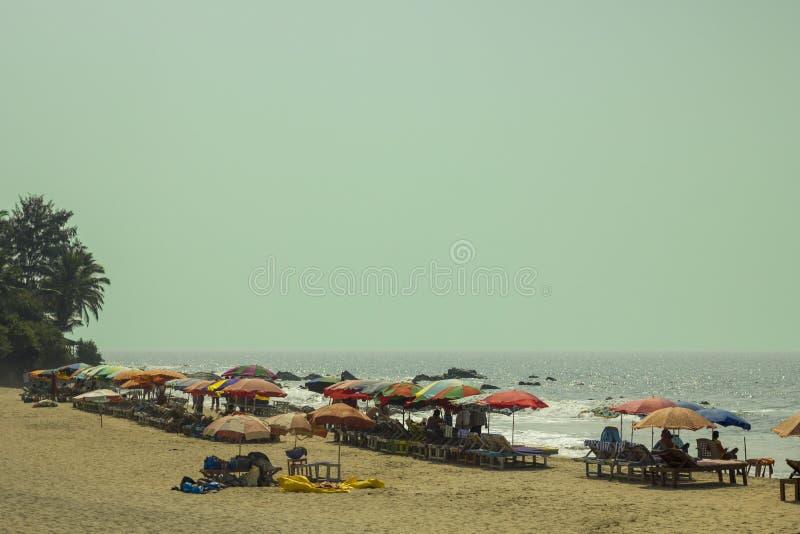 人们在黄沙的多彩多姿的沙滩伞下在海洋的背景的太阳懒人在清楚的蓝色下的 免版税图库摄影