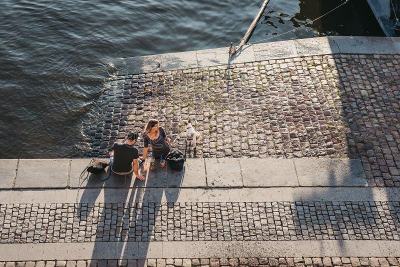 人们坐伏尔塔瓦河河的堤防在布拉格,捷克 库存照片