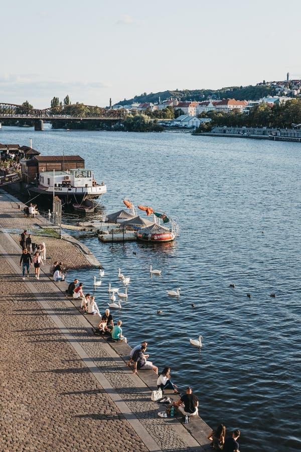 人们坐伏尔塔瓦河河的堤防在布拉格,捷克 图库摄影