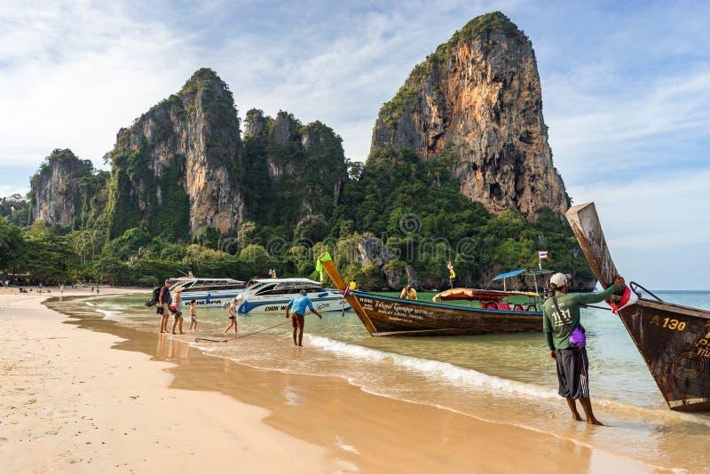 人们坐在来自热带异国情调沙滩的船上,站在 免版税库存照片
