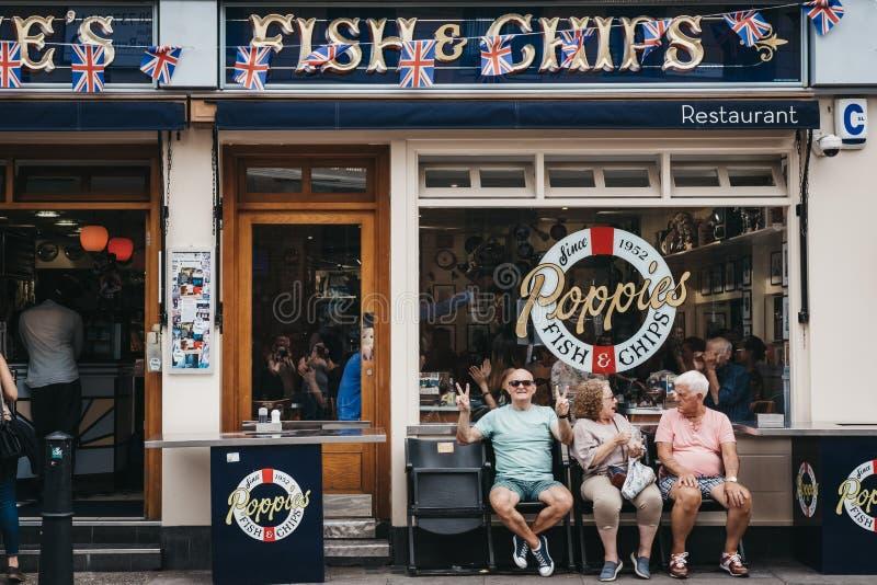人们坐在Poppie的鱼&芯片之外的一条长凳在伦敦,英国购物 库存图片