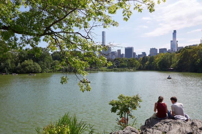人们坐岩石在池塘附近在中央公园,纽约 免版税库存图片
