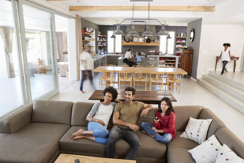 人们坐沙发和观看的电视在繁忙的家庭 免版税库存照片