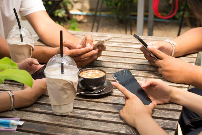 人们坐电话和饮用的咖啡在一张木桌上在餐馆 免版税图库摄影