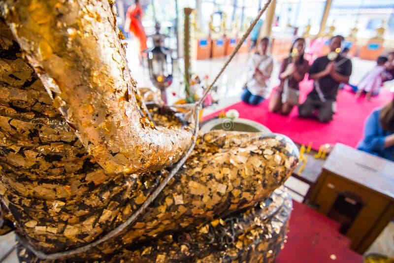 人们崇拜菩萨有金叶的雕象盖子在泰国寺庙 库存照片