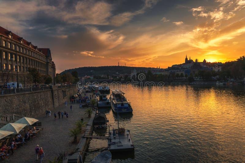 人们沿伏尔塔瓦河河走在布拉格在日落 免版税库存照片