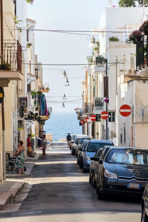 人们沿在街道上的停放的汽车走有许多的没有词条在波利尼亚诺阿马雷,意大利交通标志 库存照片