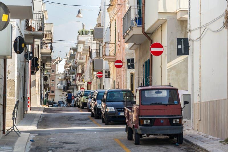 人们沿在街道上的停放的汽车走有许多的没有词条在波利尼亚诺阿马雷,意大利交通标志 免版税库存照片