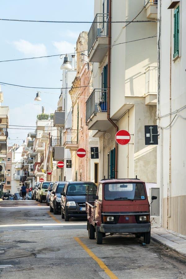 人们沿在街道上的停放的汽车走有许多的没有词条在波利尼亚诺阿马雷,意大利交通标志 库存图片