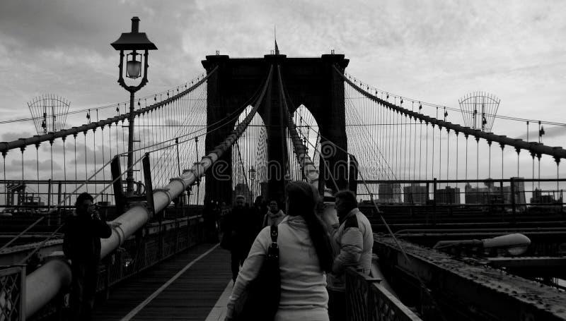 人们沿在黑&白的NYC -纽约的布鲁克林大桥走 免版税库存图片