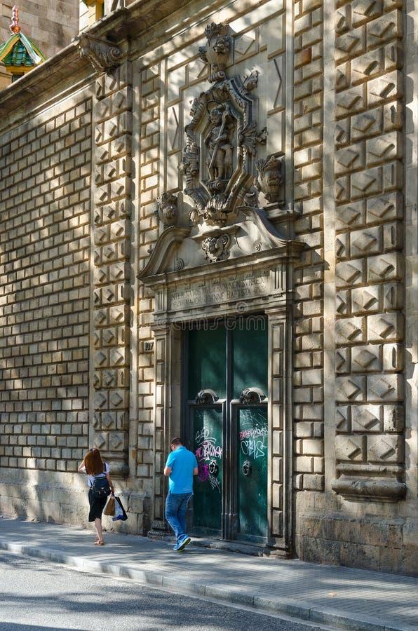 人们沿步行街道La兰布拉走在我们的伯利恒,巴塞罗那,西班牙的夫人附近教会  免版税库存图片