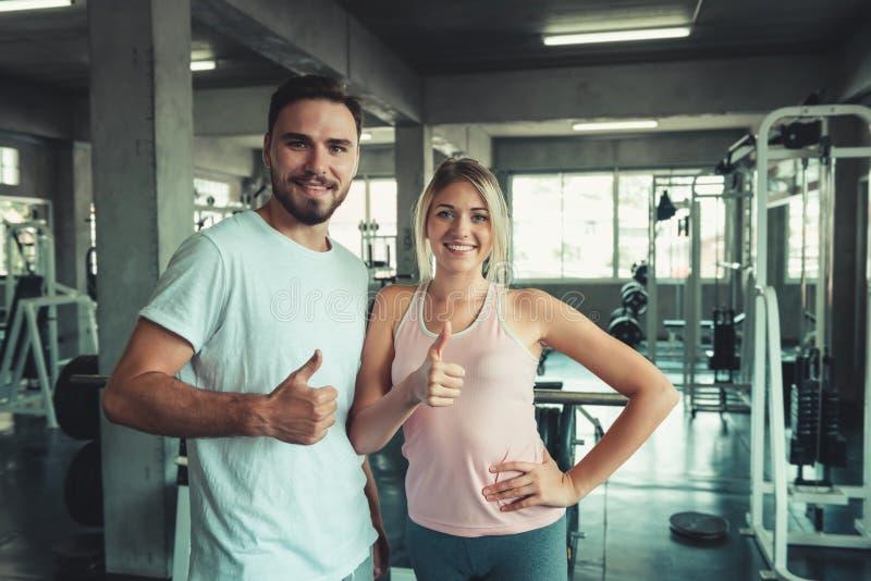 人们炫耀在健身健身房的夫妇概念给标志身体好的赞许 夫妇画象在运动服的是 库存图片