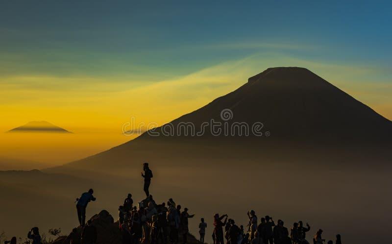 人们现出轮廓追逐与Sundoro火山的日出 免版税库存照片