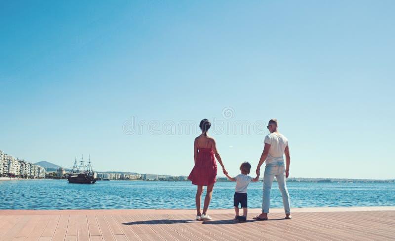 海滩的幸福家庭 人们看未来在度假暑假 父亲、母亲和孩子反对蓝色海和天空 库存照片