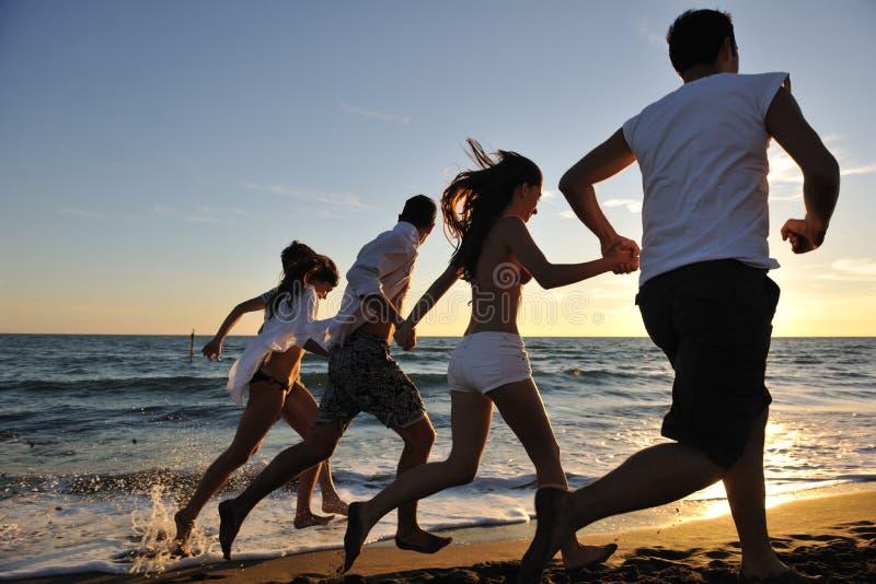 人们编组在海滩的运行中 免版税图库摄影