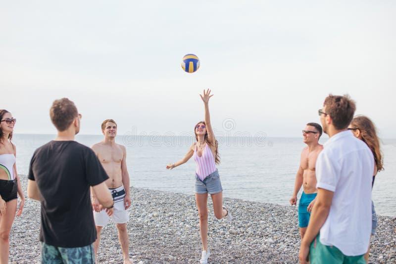 人们编组有乐趣和戏剧沙滩排球夏日 免版税库存照片