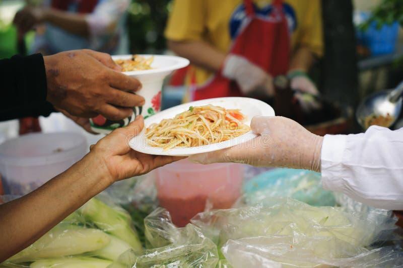 人们胜过捐赠从志愿者的食物:希望的食物概念:可怜和无家可归的人的免费食物捐赠食物 库存图片