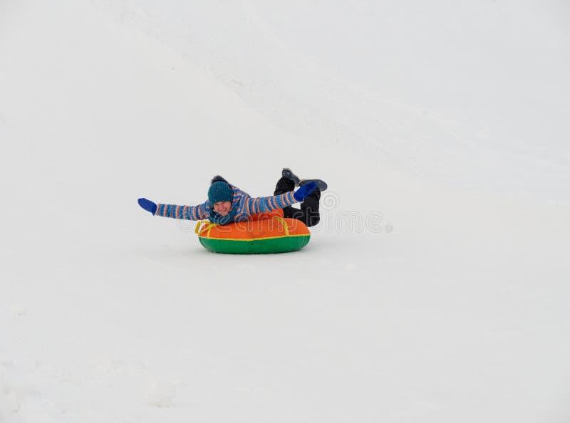 人们获得乘坐雪幻灯片的乐趣在管材 免版税库存图片