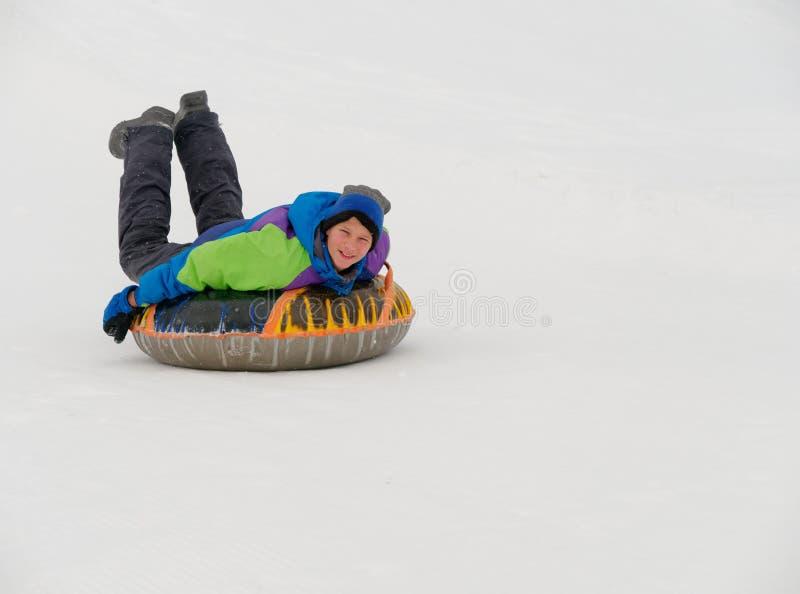 人们获得乘坐雪幻灯片的乐趣在管材 库存照片