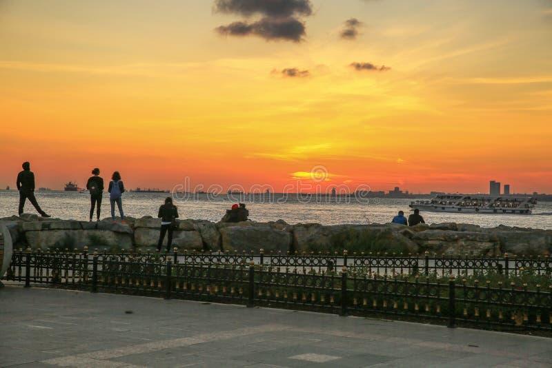 人们观看Kadikoy,日落的伊斯坦布尔风景  免版税库存图片