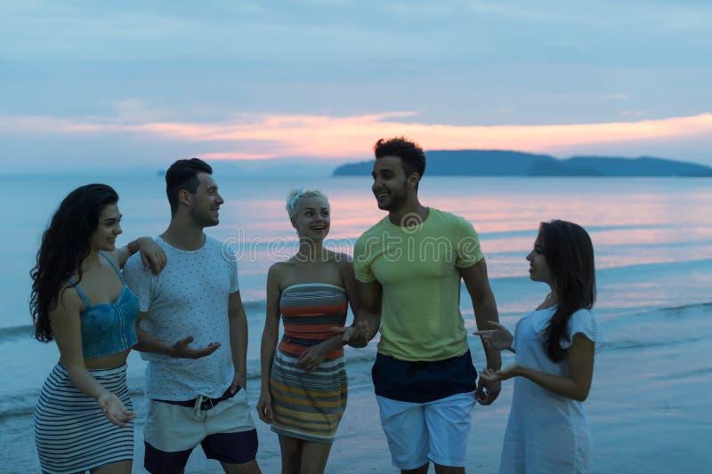人们谈话在海滩在日落,走在晚上通信的海的年轻旅游小组 库存照片