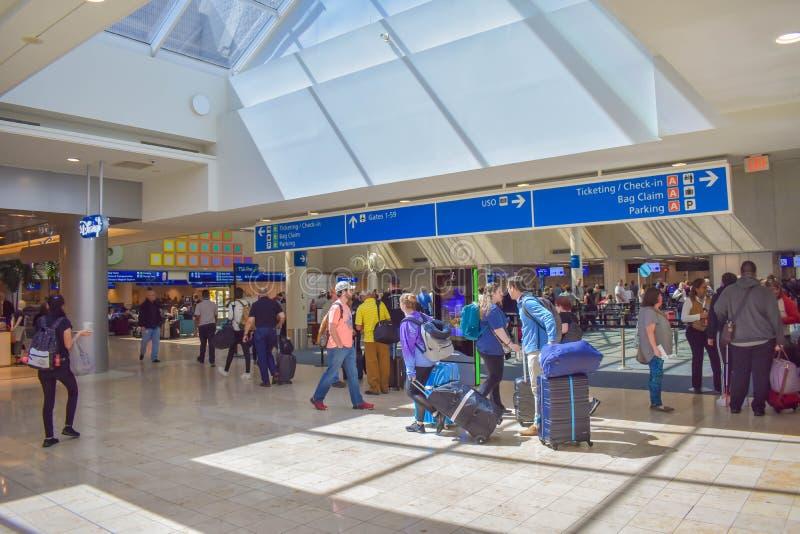 人们走到不同的终端和票顶视图的和报到蓝色标志在奥兰多国际机场3 库存图片